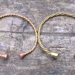 Twisted wire bracelets. The one to the left has copper and brass wires with copper terminals, the one to the right is all brass. Both about 70mm across.   I've made these in a range of sizes and from bronze, copper, brass and silver wires, with as few as one and as many as 9 wires
